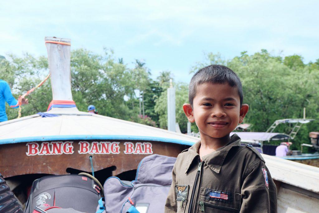 Thai kid on longtail boat Railay Beach Thailand